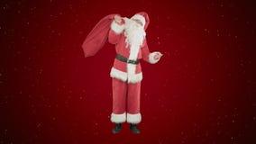 Santa Claus real que lleva el bolso grande por completo de regalos en fondo rojo con nieve Imagen de archivo
