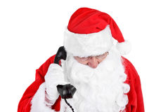 Santa claus receives a phone call Royalty Free Stock Images
