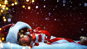 Santa Claus red bag with Christmas balls and gift box on snow Stock Images