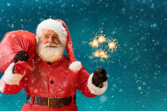 Santa Claus with a red bag of gifts and Bengal lights. Royalty Free Stock Photography