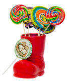 Santa Claus red boot, shoe with colored sweet lollipops, candys. Saint Nicholas boot with presents gifts. Stock Photos