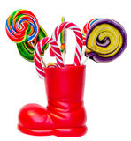 Santa Claus red boot, shoe with colored sweet lollipops, candys. Saint Nicholas boot with presents gifts. Stock Image