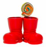 Santa Claus red boot, shoe with colored sweet lollipops, candys. Saint Nicholas boot with presents gifts. Royalty Free Stock Photos
