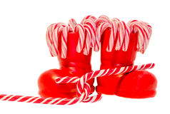 Santa Claus red boots, shoes with colored sweet lollipops, candys. Saint Nicholas boot with presents gifts. Stock Photo