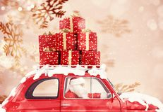 Santa Claus on a red car full of Christmas present with snowflakes background drives to deliver stock photos