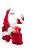 Santa Claus in red costume putting present in sack. Stock Photos