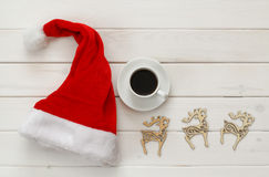 Santa claus red hat, cup of coffee next to wooden decorations Stock Photography