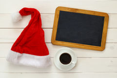 Santa claus red hat, empty blackboard next to cup of coffee Royalty Free Stock Photo