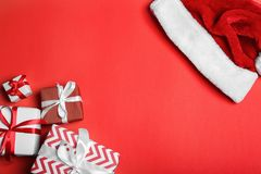 Santa Claus red hat and gift boxes on color background, flat lay. Santa Claus red hat and gift boxes on color background, top view Royalty Free Stock Photos
