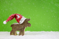 Santa Claus with red hat - wooden deer on green christmas backgr Royalty Free Stock Photo