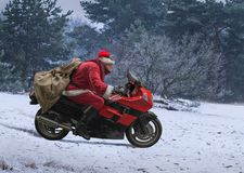 Santa Claus on red motorcycle with a sack driving along winter s stock image