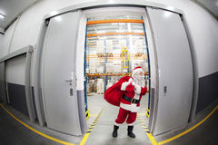 Santa Claus + red sack leaving storehouse of gifts Royalty Free Stock Image