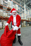 Santa Claus with red sack in storehouse Stock Images