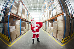 Santa Claus + red sack in storehouse  of presents Royalty Free Stock Photos