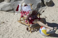 Santa Claus tanning using reflector Stock Photo
