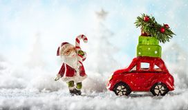 Santa Claus and red toy car carrying Christmas gifts in snowy la. Ndscape. Christmas concept with copy space stock images