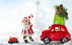 Santa Claus and red toy car carrying Christmas gifts in snowy la. Ndscape. Christmas concept with copy space stock image