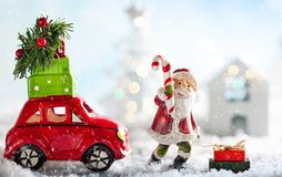 Santa Claus and red toy car carrying Christmas gifts in snowy la royalty free stock photography