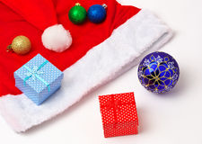 Santa Claus red and white hat, toy bubbles and christmas gifts Royalty Free Stock Photo