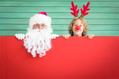 Santa Claus and reindeer child. Holding banner blank. Merry Christmas greeting card. Xmas holiday concept Stock Image