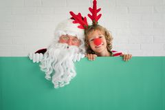 Santa Claus and reindeer child. Holding banner blank. Merry Christmas greeting card. Xmas holiday concept stock images