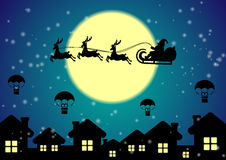 Santa Claus with reindeer flies over night city Stock Photography