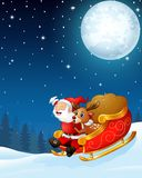 Santa claus and a reindeer riding his sleigh and carry huge sack in the night background Stock Photos
