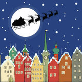 Santa Claus with reindeer sleigh through a Christmas night. Over fairytale town Royalty Free Stock Image