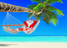 Santa Claus relax in hammock at island palm tropical beach. Santa Claus relax tanning in white mesh hammock under coconut palm tree shade at tropical paradise Stock Photo