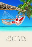 Santa Claus relax in hammock at tropical palm beach with handwritten caption of New Year 2019 on white sand, Christmas vacation stock photo
