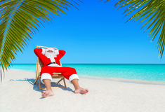 Santa Claus relax in sunlounger at sandy tropical palm beach. Santa Claus relax on wooden beach chair at ocean tropical palm beach seaside. Happy New Year and Stock Images