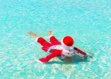 Santa Claus relax swimming in ocean water, Christmas traveling c royalty free stock photo
