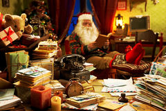 Santa Claus relaxing at home. The messy desk of Santa Claus, he reading a book Royalty Free Stock Images