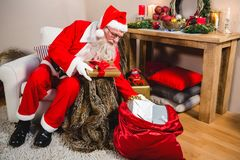 Santa claus removing gift from gift sack in living room at home Royalty Free Stock Image