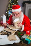 Santa Claus removing a letter. At home Stock Photos