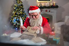 Santa Claus removing a letter. At home Royalty Free Stock Photos