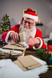 Santa Claus removing a letter. At home Stock Photo