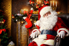 Santa claus resting. Santa Claus brought gifts for Christmas and having a rest by the fireplace. Home decoration Stock Image