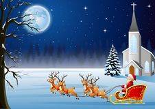 Santa Claus rides reindeer sleigh in front of church in Christmas night Stock Photography