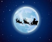Santa Claus rides reindeer sleigh silhouette against a full moon background Royalty Free Stock Images