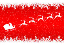 Santa Claus rides in a sleigh reindeer on red background Stock Photos