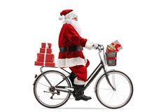 Santa Claus riding a bicycle and carrying presents. Full length profile shot of Santa Claus riding a bicycle and carrying presents isolated on white background royalty free stock photos