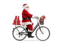 Santa Claus riding a bicycle. Full length profile shot of Santa Claus riding a bicycle  on white background royalty free stock photography
