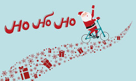 Santa Claus riding bicycle on gift way. HO-HO-HO Merry Christmas. Royalty Free Stock Photos