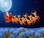 Santa Claus riding his reindeer sleigh flying in the sky Royalty Free Stock Photography