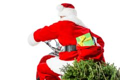 Santa Claus riding red scooter with christmas tree and big bag full of presents royalty free stock images