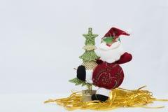 Santa Claus roja adorable con oro y el árbol de navidad verde en el fondo blanco imágenes de archivo libres de regalías