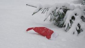 Santa Claus roja y blanca que el sombrero está mintiendo en una nieve cerca de al aire libre spruce en d3ia tranquilo, nieve se e metrajes