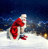 Santa Claus on rooftop shit in the chimney. Bearded Santa Claus in red costume sitting on rooftop and shit in the chimney. Humor decoration. Funny surprise Royalty Free Stock Images