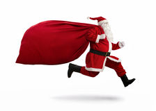 Santa Claus on the run. To delivery christmas gifts isolated on white background Stock Images